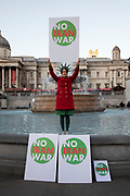 Woman dressed as the Statue of Liberty with No Iran War placard at the No to Trump, No to NATO, Hands off our NHS Demonstration on 3rd December 2019 in London, United Kingdom. Donald Trump is visiting London or the NATO Heads of State summit on the 70th anniversary of the organisation, which the Queen will be hosting a reception for NATO leaders at Buckingham Palace. Meanwhile, there is fear that Boris Johnson and Donald Trump will be in discussion about opening up the NHS to US corporations. Organisers were Together Against Trump which is a collaboration between the Stop Trump Coalition and Stand Up To Trump.
