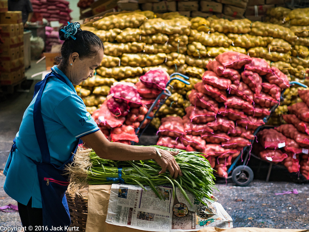 """11 AUGUST 2016 - BANGKOK, THAILAND:      A vendor bundles green onions in the produce section of Pak Khlong Talat in Bangkok. Pak Khlong Talat (literally """"the market at the mouth of the canal"""") is the best known flower market in Thailand. It is the largest flower market in Bangkok. Most of the shop owners in the market sell wholesale to florist shops in Bangkok or to vendors who sell flower garlands, lotus buds and other floral supplies at the entrances to temples throughout Bangkok. There is also a fruit and produce market which specializes in fresh vegetables and fruit on the site. It is one of Bangkok's busiest markets and has become a popular tourist attraction.       PHOTO BY JACK KURTZ"""
