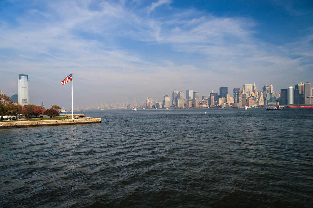 American Flag and the New York Skyline in USA. In flag red symbolizes Hardiness and Valor, white symbolizes Purity and Innocence and blue represents Vigilance, Perseverance and Justice.