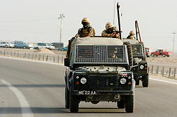 """British soldiers from The East and West Riding Regiment, Territorial Army wearing desert camouflage, Kevlar helmet and body armor, carrying SA80 assault rifle which is fitted with SUSAT sights, Travel in convoy in  """"Soft Skin"""" Land Rovers with troops manning the top cover position. The convoy is moving from Basra Air Station to Shibah Logistics Base  during Op-Telic in March 2005"""