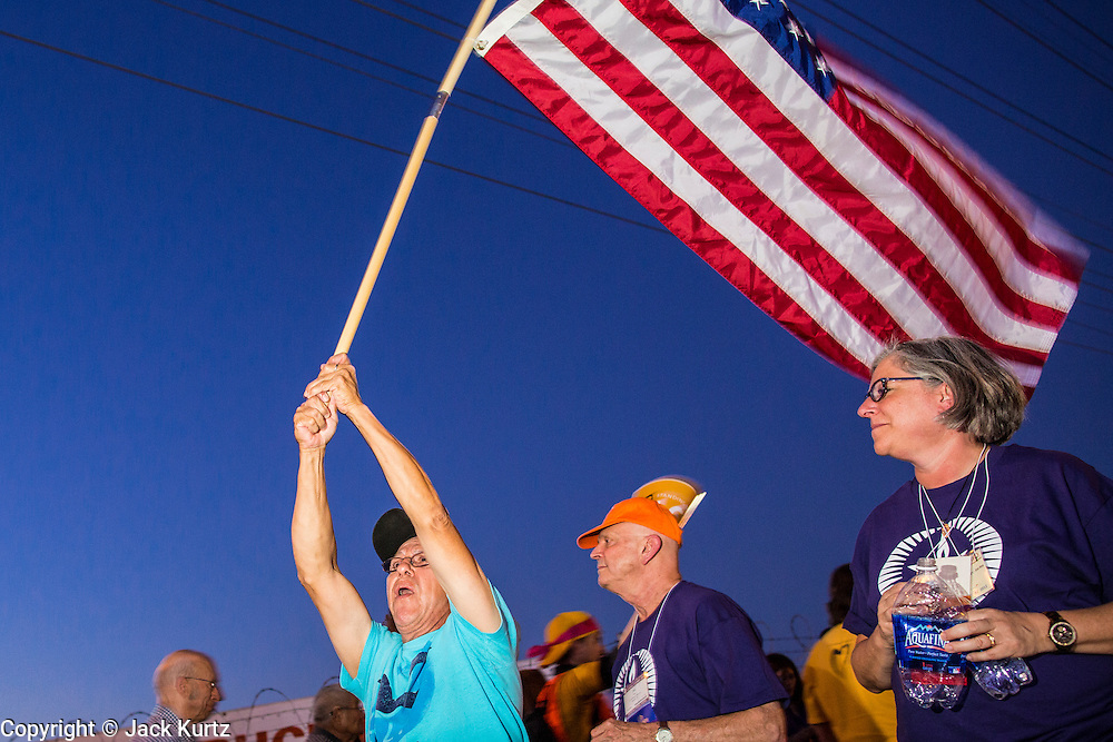 """23 JUNE 2012 - PHOENIX, AZ:  An opponent of Maricopa County Sheriff Joe Arpaio waves an American flag during a protest against the Sheriff in front of the county jails Saturday. About 2,000 members of the Unitarian Universalist Church, in Phoenix for their national convention, picketed the entrances to the Maricopa County Jail and """"Tent City"""" Saturday night. They were opposed to the treatment of prisoners in the jail, many of whom are not convicted and are awaiting trial, and Maricopa County Sheriff Joe Arpaio's stand on illegal immigration. The protesters carried candles and sang hymns.     PHOTO BY JACK KURTZ"""