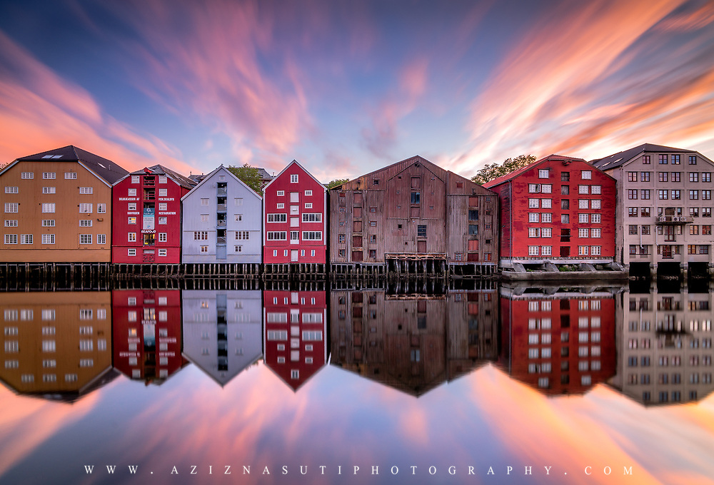 Trondheim with picturesque, tiny, wooden houses. This idyllic neighbourhood on the east side of the Nidelva river features old timber buildings, originally the homes of the working class. Now restored, Bakklandet is a charming mixture of houses, shops and cafés.<br /> Nidelva river cuts through the city, winding its way along the Nidarosdomen park and picturesque areas, with the historic, wooden wharf houses lining its sides towards the mouth at the Trondheim fjord, and the beautiful, wooden bridge amle Bybrocrossing the river. Please feel free to check my photos here or find me by: |Website| ,|Facebook page| , |Instagram| ,|Google+| ,|Twitter |.