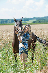 Young woman stroking her brown horse standing on wheat field and smiling, Bavaria, Germany