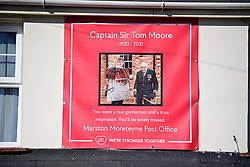 © Licensed to London News Pictures. 27/02/2021. Marston Moretaine, UK. The funeral cortege carrying the coffin of Captain Sir Tom Moore passes members of the public in his home town of Marston Moretaine, on it's way to Bedford Crematorium for a funeral service. Captain Tom, who raised £32 million pounds for the NHS by walking laps of his garden during Coronavirus lockdown, died in hospital aged 99. Photo credit: Ben Cawthra/LNP