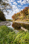 Vibrant fall colors reflect in Mill Creek, upstream of Lower Falls in Cataract Falls State Recreation Area, near Cloverdale, an hour southwest of Indianapolis, in Indiana, USA. Autumn foliage colors were brilliant but water volume was low for this photo October 21, 2015. The park's limestone outcroppings formed millions of years ago when the region was covered by a large shallow ocean. This panorama was stitched from 7 overlapping photos.