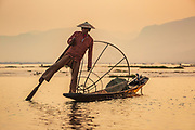 Sunset shot of traditional style of fishing and leg-rowing on Lake Inle, Myanmar