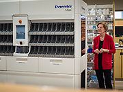 28 DECEMBER 2019 - URBANDALE, IOWA: US Senator ELIZABETH WARREN (D-MA), looks at a Parata Max vial filling robot, which helps pharmacists quickly and safely complete patients' prescriptions, at the Medicap Pharmacy in Urbandale, IA. Warren is campaigning in Iowa this weekend to support her effort to be the Democratic nominee for the US presidential race in 2020. Iowa traditionally hosts the first presidential selection event of the campaign season. The Iowa caucuses are Feb. 3, 2020.        PHOTO BY JACK KURTZ