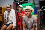 09 JUNE 2014 - YANGON, MYANMAR: Porters in the San Pya Fish Market (also spelled Sanpya) wait for work. San Pya Fish Market in Yangon is one of the largest wholesale fish markets in Yangon. The market is busiest in early in the morning, from before dawn until about 10AM.    PHOTO BY JACK KURTZ