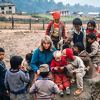Meredith Wiltsie & 3-year old son Ben are surrounded by curious Sherpa children while trekking  in the Khumbu Region of Nepal,