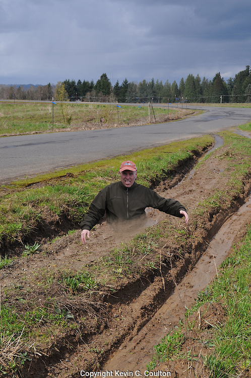 """Humorous photograph of a man stuck waist deep in a muddy tire rut visually depicting the saying """"Stuck in a rut!"""""""