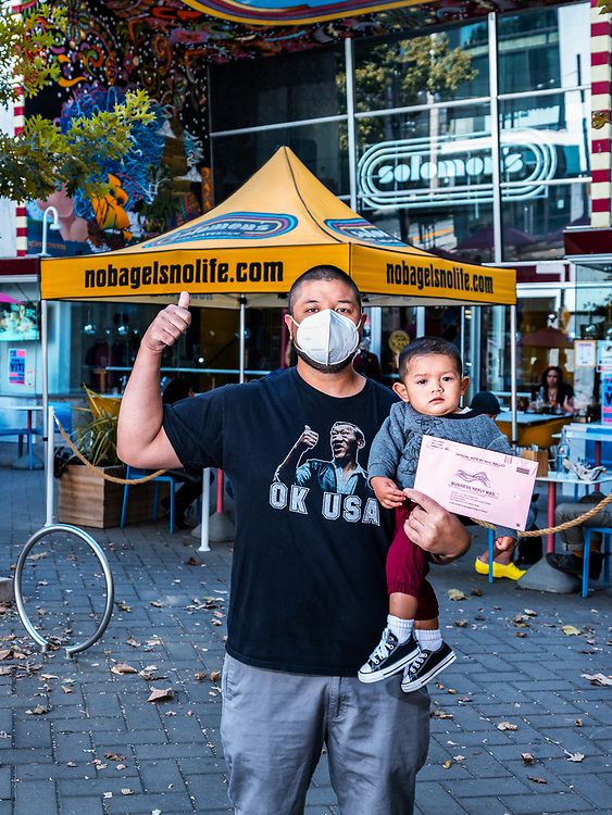 """Kooney (36). Second-gen Lao-American. This is my bodyguard, Ezra (16 months) the third generation.<br /> <br /> In the last Presidential Election. I am guilty of being one of the selfish uninformed voters just bubbling in random circles as if it were a standardized test.This time it's a lot different.I read somewhere that body fat and white hairs are good indicators of being wise. So,I've amassed a whole lotta both. Not sure if I accumulated any wisdom tho. Prolly just a placebo.<br /> <br /> I vote now but, with a purpose. Not for me but, for my family and community in mind.<br /> <br /> The minority vote is a smaller share but it is a path to empowerment.Our voices are definitely underrepresented, we must continue to vote and press the issues we feel are important.We all want to be heard, to be acknowledged, to matter. For example the Secret War in Laos; just like today's issues, we want accountability.<br /> <br /> The Pandemic has impacted my life, I've been furloughed from my job and I'm not certain as to when I'll be recalled back to service. The silver lining is now I get to practice some personal virtues, (Humility and Patience).Being isolated at home was bad for my mental and physical health.That's why I'mthankful to have secured temporary work. I just need to keep busy.<br /> <br /> With regard to what is happening in this country, I would like the (UNITED) States of America, to experience U-N-I-T-Y and COEXIST. We seem to be moving in opposite directions and the change for a """"GREAT"""" America is going nowhere fast!<br /> <br /> Stay positive, not (COVID). But know that better days are to come."""
