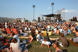 "Wide view of the ball field facing the stage. Deadheads and fans relaxing before the Grateful Dead Concert begins later in the day as the sun grows warmer. At Roosevelt Stadium on 4 August 1976. Showing entire sound array of Hard Truckers Speakers. This image appears in DK Publishers ""The Illustrated Trip"" The Grateful Dead as a 2 page spread."