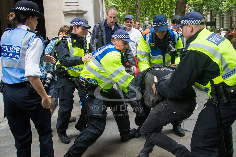 London, June 24th 2017. Anti-fascist protesters counter demonstrate against a march to Parliament by the far right anti-Islamist English Defence League. PICTURED: Police wrestle a masked anti-fascist to the ground during a scuffle with members of the EDL.