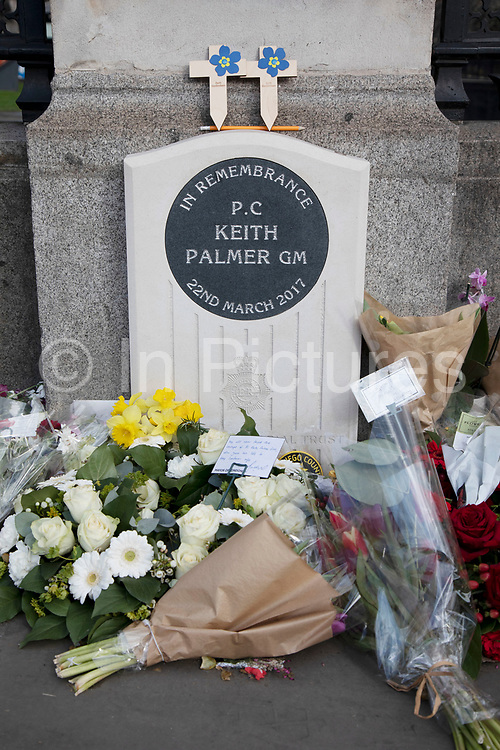 Flowers laid at the memorial in remembrance to PC Keith Palmer in Westminster, London, England, United Kingdom. Keith Palmer, was a British police officer who was posthumously awarded the George Medal, the second highest award for gallantry. Though unarmed, he stopped a knife-wielding terrorist from entering the Palace of Westminster during the 2017 Westminster attack. He died from wounds he received in this attack.