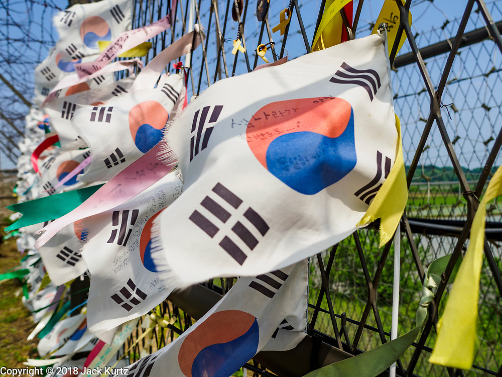 09 JUNE 2018 - IMJINGAK, PAJU, SOUTH KOREA: South Korean and prayer flags hang on fence near the northernmost point on the South Korean side of the Korean DMZ in Imjingak. The banners are left by visiting South Koreans and some tourists. Imjingak is a park and greenspace in South Korea that is farthest north most people can go without military authorization. The park is on the south bank of Imjin River, which separates South Korea from North Korea and is close the industrial park in Kaesong, North Korea that South and North Korea have jointly operated.     PHOTO BY JACK KURTZ