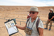 Archaeologist Dr. Uzi Avner at the Leopard Temple prehistoric cult site in the Uvda valley desert region, Negev, Israel. Dr. Avner was one of the excavators of this site in the 1980s. This site has been dates to have been dated to the Bronze age 6th Millennia BC and was in use for circa 4000 years. The name of the site is due to the finding of 16 animal figures 15 of them identified as [female] leopards and one as a hinted or dead ibex