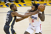 Golden State Warriors forward Kevin Durant (35) strips the ball from LA Clippers forward Montrezl Harrell (5) at Oracle Arena in Oakland, California, on February 22, 2018. (Stan Olszewski/Special to S.F. Examiner)
