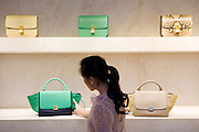 HONG KONG - MAY 04: Patricia Szeto shops for a handbag in a fashion store in Landmark shopping mall in Central business district, on May 4, in Hong Kong. (Photo by Lucas Schifres/Pictobank)