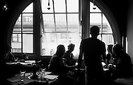 """29 SEPT, 2003 -- SEATTLE -- Patrons fill a corner table at Matt's in the Market, a well-known restaurant in Seattle's Pike Place Market in September 2003. """"Matt's is like attending a dinner party where everyone crowds into the kitchen,"""" says a reviewer from Sunset Magazine. """"And the fare has turned this place into a local mecca."""" Image © copyright 2003 Sid Hastings."""