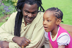 Single father sitting on park bench next to young daughter,