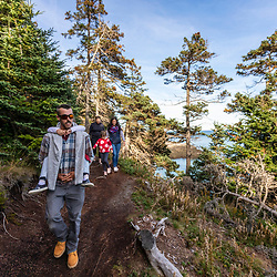 A couple hikes with their two daughters on a trail at Quoddy Head State Park in Lubec, Maine.