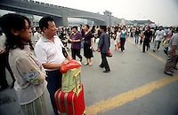 A couple wait for their train among the crowds outside Xian train station.