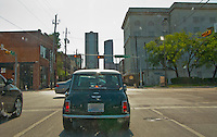 driving a Classic Mini Cooper auto through downtown Dallas, Texas with bug splats on the windshield.