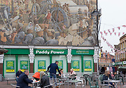 A Paddy Power betting outlet and the mural about Dartford's industrial heritage by Gary Drostle on One Bell Corner in the Kentish town's pedestrianised High Street, on 3rd October 2019, in Dartford, Kent, England. The mural is entitled 'One Town That Changed The World' (2000) and celebrates the unique Industrial heritage of Dartford in Kent. London artist Gary Drostle is an award winning artist specialising in site specific art, painted murals, floor and wall mosaics and mosaic sculptures.