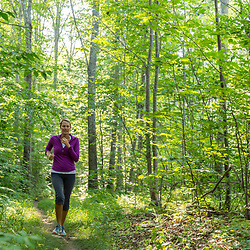 A woman runs on a forest trail at Barker's Farm in Stratham, New Hampshire.