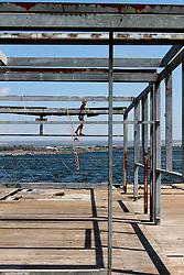 Bambino in costume da bagno sul pontile galleggiante del porto di Taranto, arrampicato ad una struttura metallica.