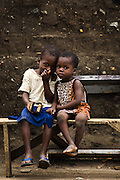 Two boys sit on a bench in a rural area near Kpong, Ghana on Wednesday June 17, 2009.