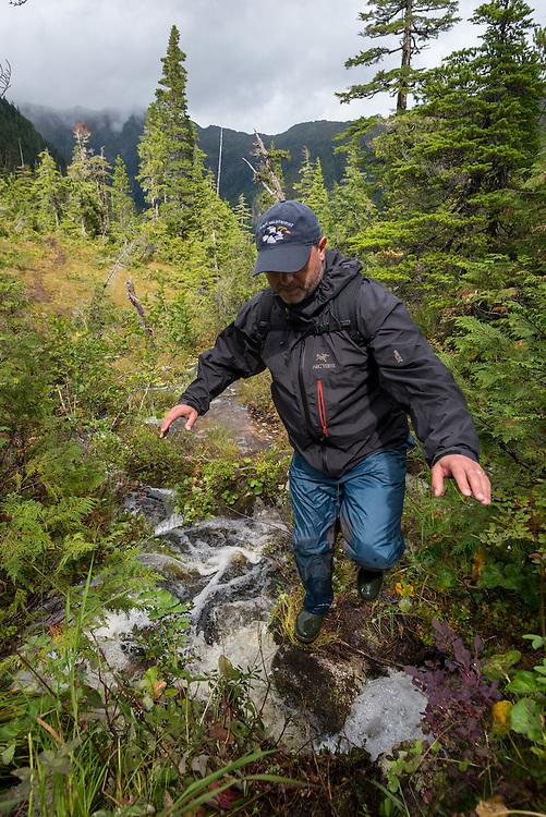 Hiking on a wet and muddy Sadie Lake Trail on Baranof Island, Alaska.