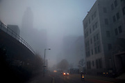 Thick fog in London's financial district in Docklands. The elevated tracks of the DLR (Docklands Light Railway) above making a peaceful yet eerie landscape atmosphere as towers appear and disappear. Modern commercial architecture is releaved through a mist which lasted tthrough the entire day.