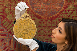 "© Licensed to London News Pictures. 23/10/2020. LONDON, UK. A staff member presents ""A Highly Important Royal Mughal Planispheric Astrolabe, Signed By Diya Al-Din Ibn Muhammad Qa'im"", India, Lahore, Dated 1068 AH (1657 AD), (Estimate GBP200,000-300,000), at Sotheby's, New Bond Street during the preview of their auction of Treasures from the Islamic World on October 27.  Photo credit: Stephen Chung/LNP"