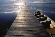 The dock at Ambergris Cay, Belize. Tourist riding a rented bicycle on the dock.  Central America.