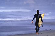 Male surfer walking on a beach in San Diego, CA.