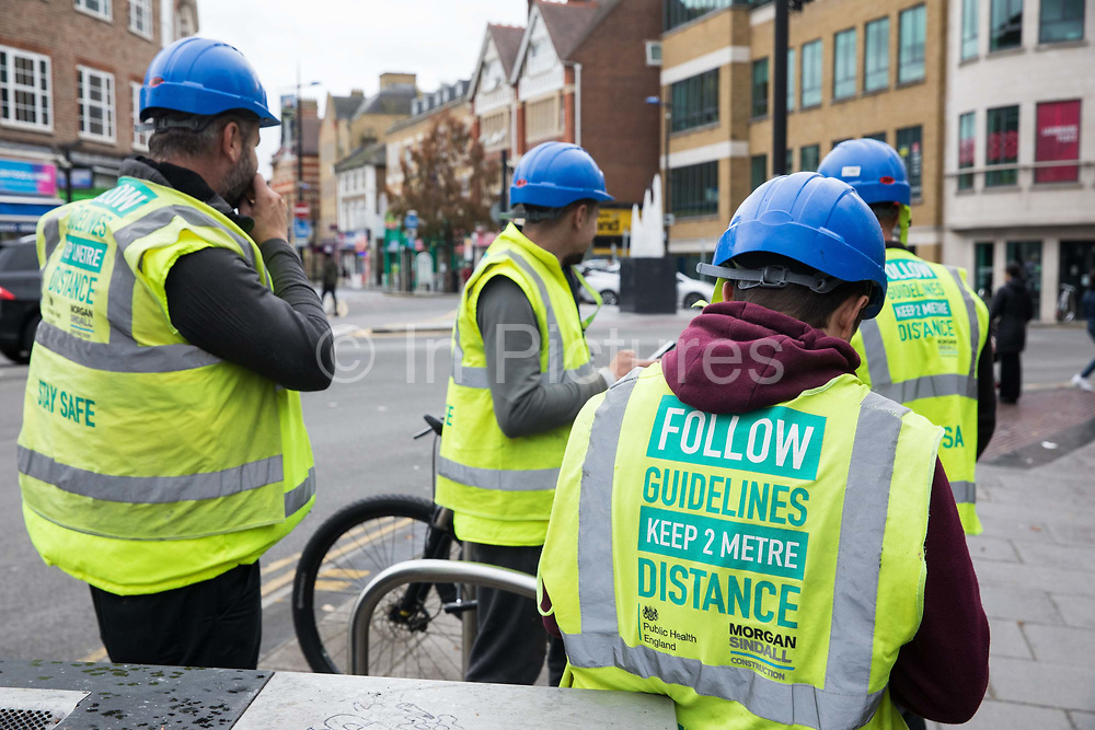 Construction workers wear high-visibility jackets reminding of the need to observe social distancing to help prevent the spread of the coronavirus on 23 October 2020 in Slough, United Kingdom. The Government has announced that Slough will change its COVID Alert Level status from Tier 1 Medium Alert to Tier 2 High Alert with effect from 00:01 on Saturday 24 October following a sustained rise in COVID-19 cases resulting in an infection rate of 153 cases per 100,000.