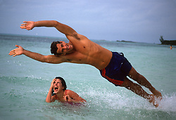 man leaping over a woman in the ocean