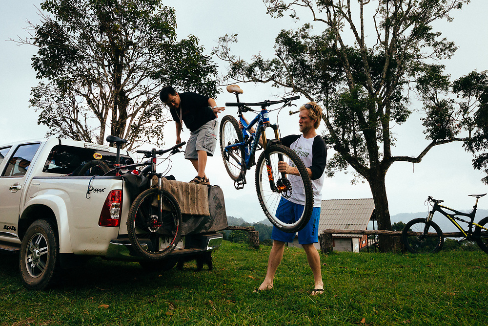 Andrew Whiteford and Mr. Sak unload mountain bikes at the top of the road to Doi Bakia in the jungle near Ban Sop Gai, Thailand.