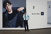 A young man stops to smoke a cigarette in front of a hoarding for the clothing retailer Gap, in central London. The male model on the screen ad adjusts his jacket and looks to the viewer while the young lad smokes his tobacco roll-up looking at us suspiciously alongside the Gap slogan 'Back to Blue'. Gap Inc. or The Gap, is an American multinational clothing and accessories retailer. It was founded in 1969 by Donald G. Fisher and Doris F. Fisher and is currently headquartered in San Francisco, California.