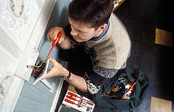 Electrician doing repair work in council flat, UK