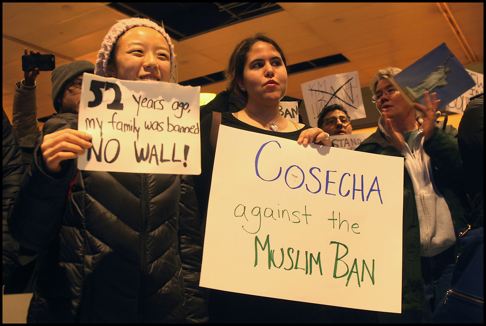 """At Boston's Logan Airport, hundreds of protesters assembled outside the foreign arrivals gate for hours Saturday night, chanting """"Let them in"""" as protesters gathered at airports across the nation on January 27, 2017, to demonstrate against President Donald Trump's executive order temporarily banning foreign refugees, as well as travelers from seven predominantly Muslim countries."""