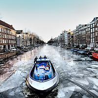 Nederland, Amsterdam , 28 januari 2013..v.l.n.r. Tom, Ruud en Hennie op hun IJsbreker door de Amsterdamse grachten..Three men on their ice-breaker breaking the ice of the Amsterdam canals.