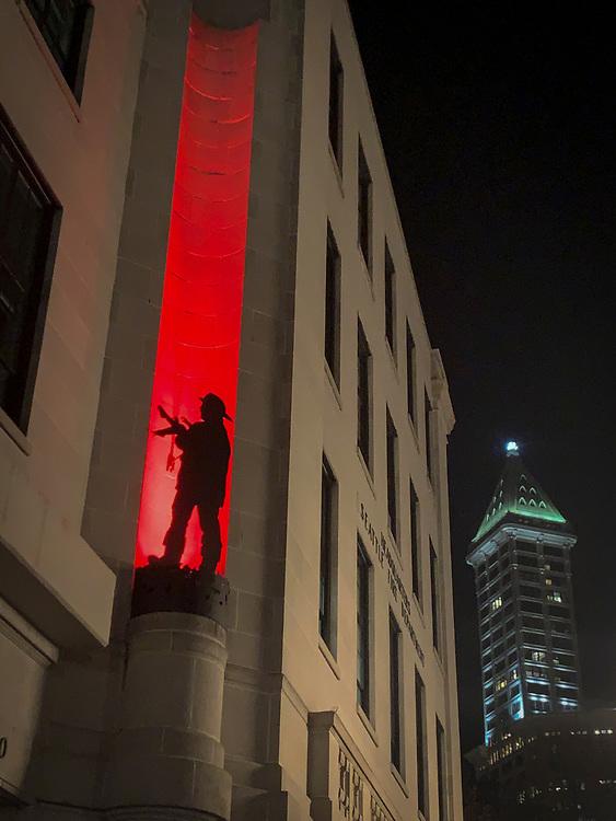 United States, Washington, Seattle, Fireman statue and Smithi Tower at night