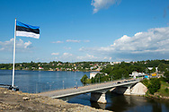 Narva, Estonia - July 24, 2015: View from Estonia toward the Russian side of the Narva River. Cars wait on the bridge to pass through the control gate, traveling from the Estonian city of Narva to the Russian city of Ivangorod. An Estonian flag is on the left.