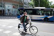 Een man fietst met een kind voorop door Utrecht.<br /> <br /> A man is cycling with a child on his bike.