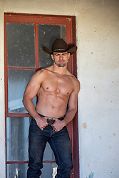 muscular shirtless cowboy standing in a large rustic window