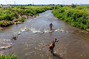 Children cooling down in the river Bodva during tropical temperatures located close to their Roma settlement in Moldava nad Bodvou. From about 800 inhabitants of the segregated settlement 'Budulovska Street' (2014) are roughly 392 children up to the age of 16 years.