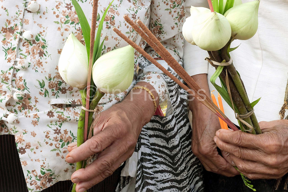 """Two elderly women hold lotus flowers, candles and incense sticks as offerings before they circumambulate Pha That Luang three times in honour of Buddha at the That Luang festival, Vientiane, Lao PDR. Pha That Luang is the national symbol and most important religious monument of Laos. Vientiane's most important Theravada Buddhist festival, """"Boun That Luang"""", is held here for three days during the full moon of the twelfth lunar month (November). Monks and laypeople from all over Laos congregate to celebrate the occasion with three days of religious ceremony followed by a week of festivities, day and night. The procession of laypeople begins at Wat Si Muang in the city centre and proceeds to Pha That Luang to make offerings to the monks in order to accumulate merit for rebirth into a better life."""