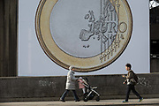 A mother and child walk past a giant Euro coin, an artwork by Danish artists Superflex, hanging from the hayward Gallery on Waterloo Bridge, on 3rd February 2017, London, England. For the third Waterloo Billboard Commission, the work is a euro coin with its value conspicuously absent – made by the group in 2012, in response to the Greek financial crisis – has gained new resonance since the UKs decision to leave the EU. The billboard is the third in a series of large-scale commissions by international artists, occupying the prominent billboard site next to Hayward Gallery.